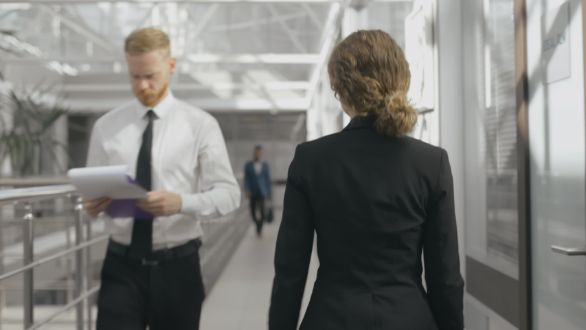 Back view of female entrepreneur or office worker walking in modern office corridor to the meeting. Other office workers go towards