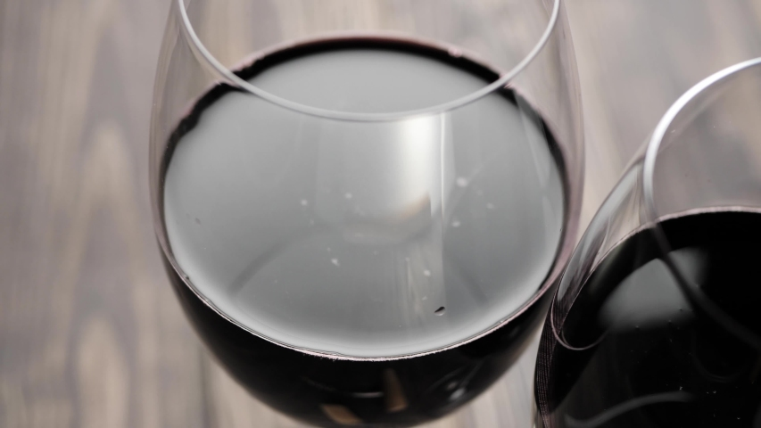 Luxury red wine. Two wine glasses of red wine, made from delicious red grapes on the table against black background. Camera moves from one glass to other. Slow motion. Close up. 4K | Shutterstock HD Video #1043196490