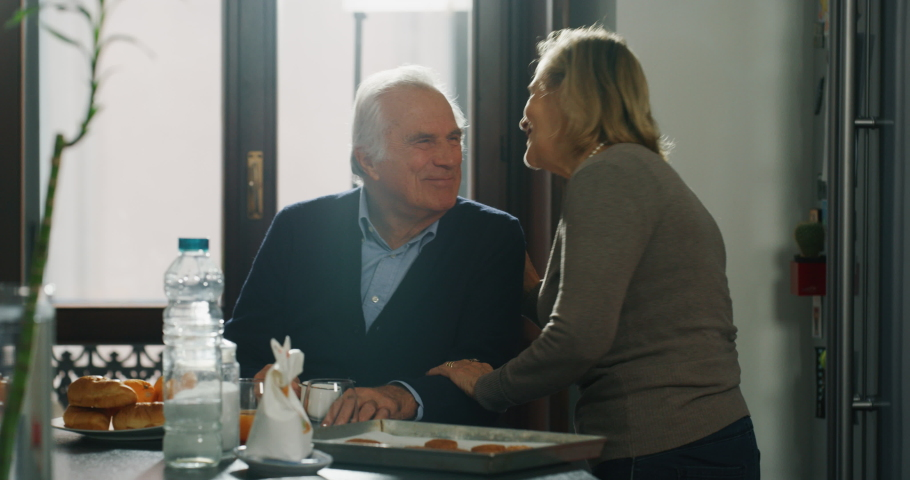 A mature senior couple in love is enjoying to have a breakfast together in a kitchen just wake up in a morning at home.