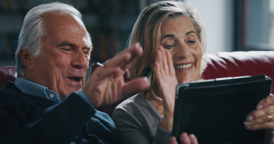 Close up of happy mature senior couple is making a selfie or video call with a tablet in living room at home.