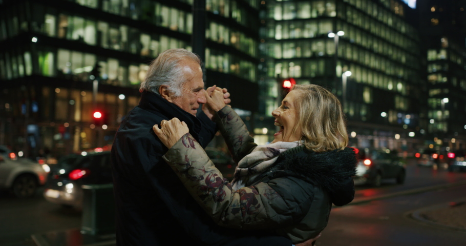 A lovely senior couple is dancing with classic music in the middle of traffic lights to celebrate their forever love and happiness in a city center in the evening. Concept: endless love, marriage,life