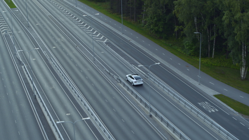 Aerial Drone View of a Modern Luxury White Electric Crossover Driving on Urban Road during a Cloudy Day. Battery Powered Car Exits a Bridge on a Highway. Futuristic SUV with Autopilot.
