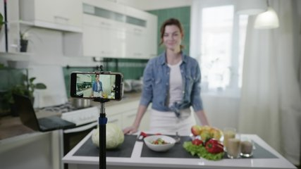 home blog, modern attractive housewife writes vlog video on mobile phone, talks about healthy foods and losing weight, shows diet plan while standing at table with fresh vegetables in kitchen