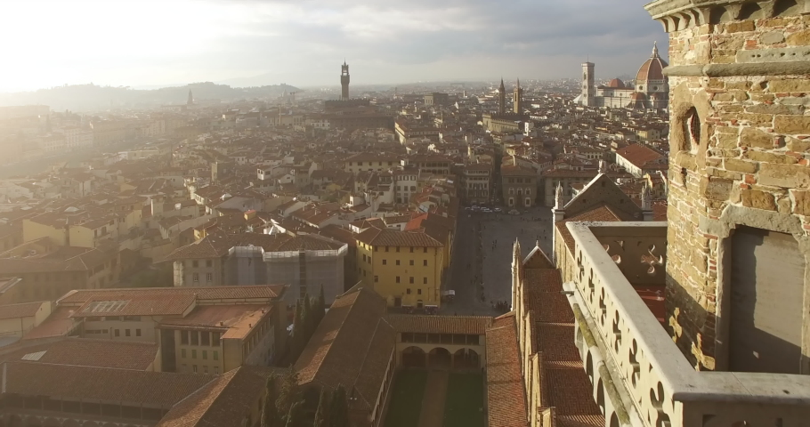 Drone flies toward the pointed tower of Basilica of Santa Croce and over the cityscape of famous landmark of Italy, the city of Florence. Another attraction - the Florence Duomo is seen ahead. 4K | Shutterstock HD Video #1043224510