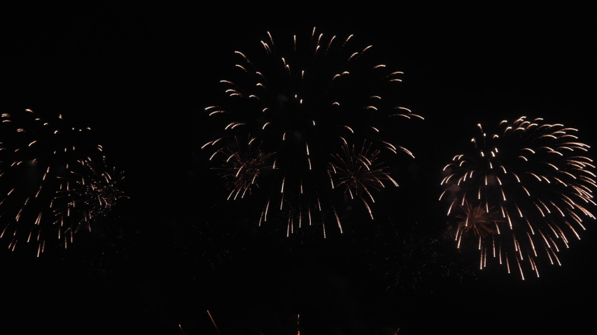 4k. Golden big shiny fireworks with bokeh lights in the night sky. Glowing firework show. New Year's Eve fireworks celebration. Fireworks Festival. Royalty-Free Stock Footage #1043238355