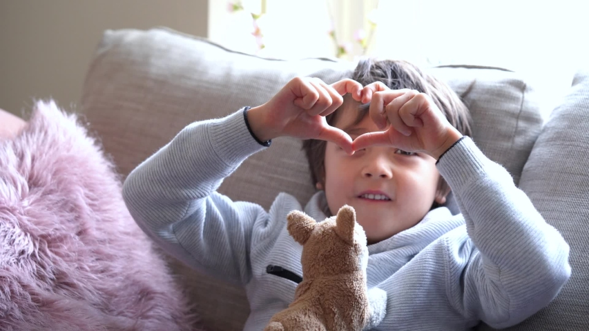 Cute little boys sitting on sofa making heart shape gesture with bright light morning, Young boy looking through the heart from hands to the camera. Child hands showing heart.
