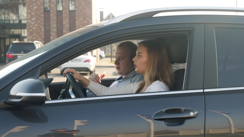 4k footage of male driving instructor sitting on passenger seat in car and showing way to female student in driving school | Shutterstock HD Video #1043301895