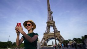 Slow motion of happy young woman tourist walking in France and talking with friend via video call on smartphone using roaming.Positive traveler waving hand at front camera standing near Eiffel Tower