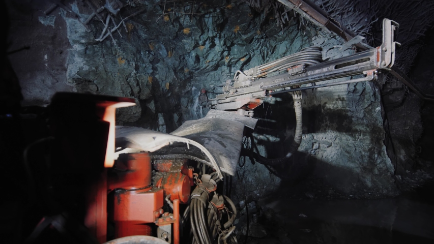 Rock surface drilling machine used to drill blast holes at mine tunnel. Mining excavator drills a hole in the rock in copper pyrite mine. A large industrial drill boring into a rock wall.