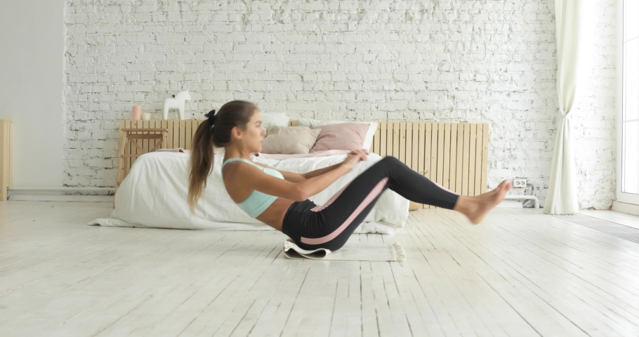 Athletic girl in sportswear is pumping the abdominals. Fit woman is doing abs exercises flexing legs on floor at home, side view. Sport and fitness. Training, workout and wellness concept. | Shutterstock HD Video #1043307973