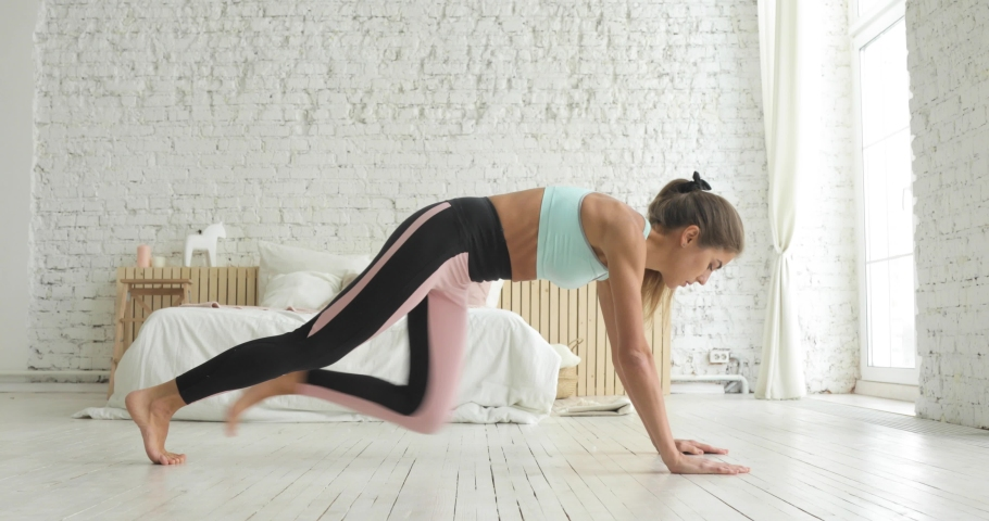 Young woman making plank flexing legs exercise in dynamic at home, side view. Sporty fit girl doing fitness aerobic exercises in bedroom. Home workout, training and wellness concept.