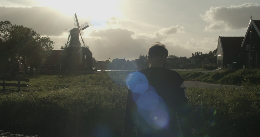 Young stylish man wearing black jeans and hoodie posing in front of wing mills in the Netherlands. Summer evening light. | Shutterstock HD Video #1043312536