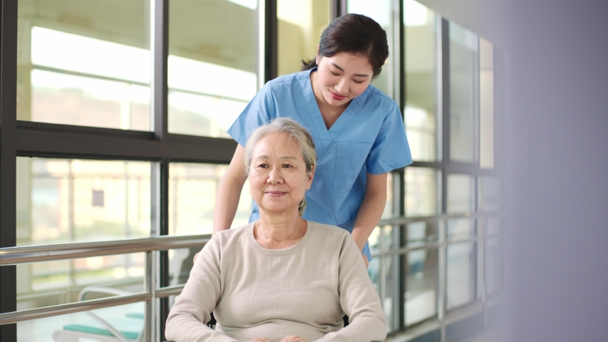friendly asian worker talking to wheelchair bound senior resident in hallway of assisted living facility Royalty-Free Stock Footage #1043314183