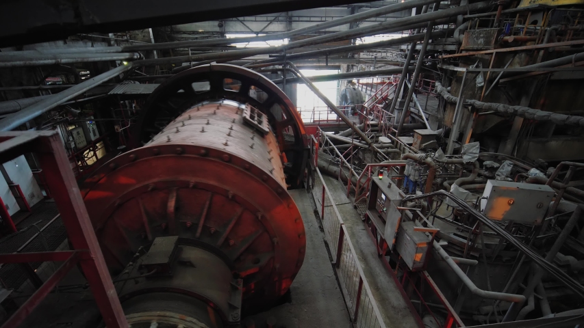 Big ball mill grinds ore on the ore-dressing factory. Industrial grinder at manufacture rotating. Copper processing industry.