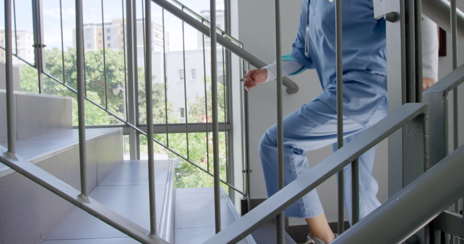 Low section side view of a female healthcare worker in uniform, wearing scrubs running up the stairs in a hospital. Healthcare workers in the Coronavirus Covid19 pandemic
