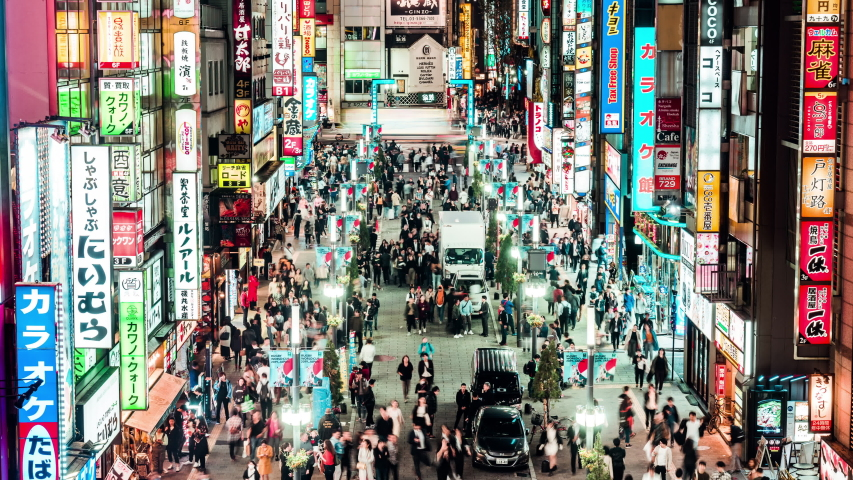 Tokyo, Japan - Nov 2, 2019: time-lapse of crowd Asian people walk on Kabukicho street, Shinjuku red-light entertainment district. Tokyo nightlife tourist attraction, Japan travel destination. Zoom out