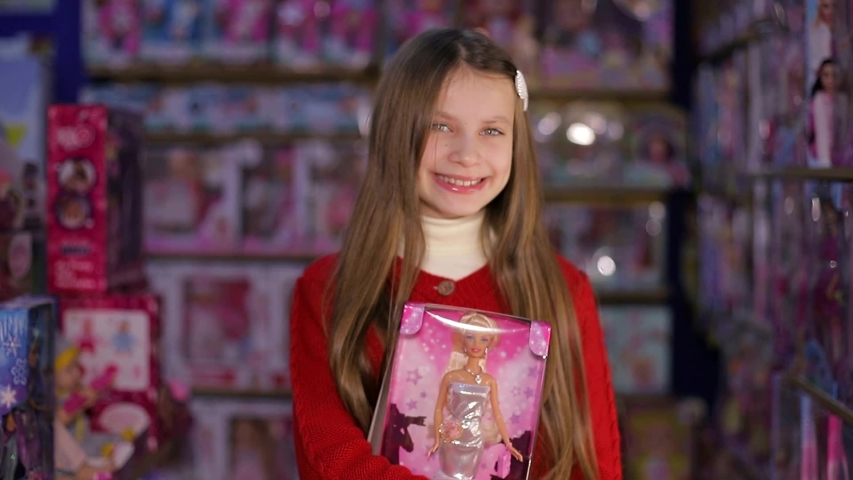 Ukraine, Ternopil December 20, 2019, Beautiful and cute girl bought the most popular doll in the world. A toy, the best gift. Good shopping