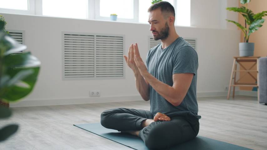 Slow motion of serious young man meditating at home moving hands in namaste with closed eyes sitting on yoga man in cozy apartment. People and relaxation concept. | Shutterstock HD Video #1043386024