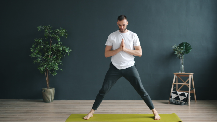 Slow motion of yoga student good-looking guy in sportswear practising asanas standing on mat in cozy studio exercising alone. People and sports concept. | Shutterstock HD Video #1043395579