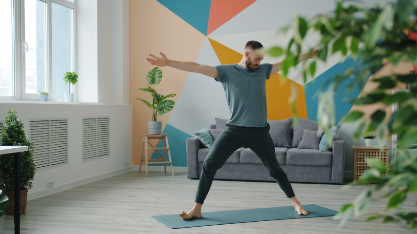 Professional yoga instructor in sports clothing is exercising at home doing complex of asanas alone standing on mat. Activity and apartment concept. | Shutterstock HD Video #1043395585