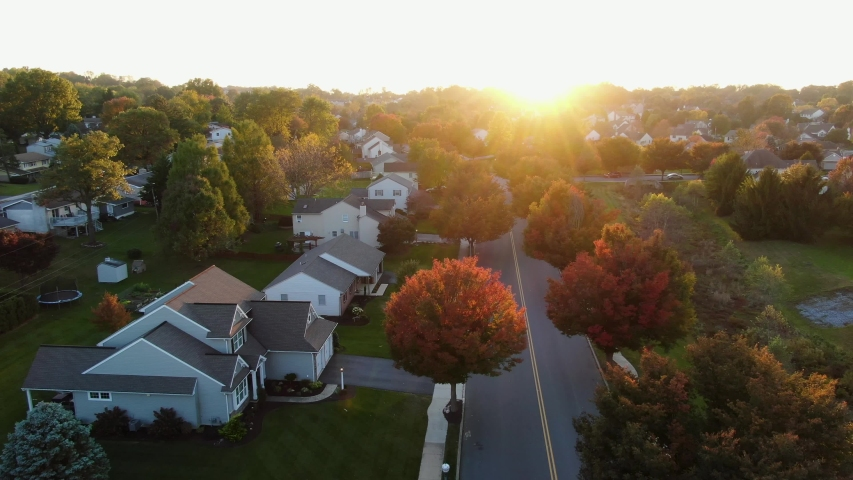 Sunset starburst highlights autumn neighborhood scene with homes and colorful trees, cars and trucks on street at intersection, aerial drone shot | Shutterstock HD Video #1043396089