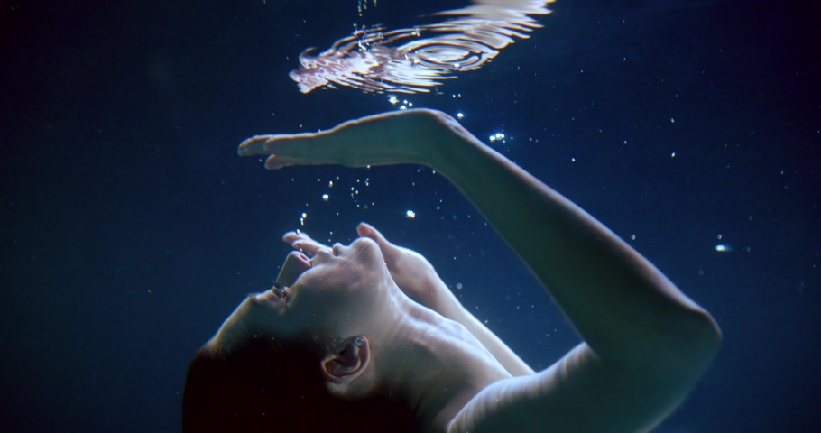 young woman is approaching to reflection of her face underwater