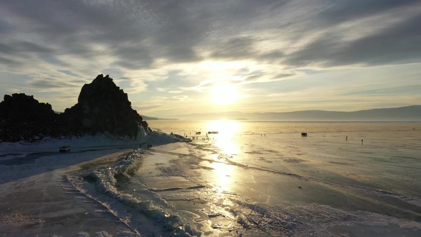 Frozen Lake Baikal, Cape Burhan Shaman rock of Olkhon Island. Tourists on lake Baikal, walking on the ice of the lake.. The famous natural landmark Russia. Blue ice with deep cracks. No color grading