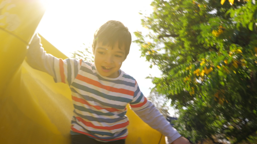 A kid going down a yellow slide in slow motion