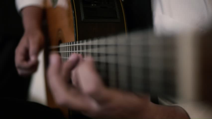 A man plays a spanish style accoustic guitar with skillful fingers
