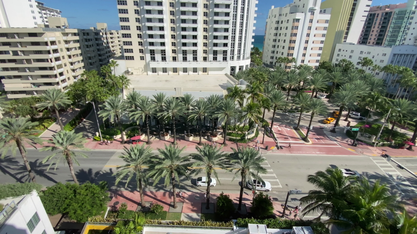 A high angle view of traffic and pedestrians on Collins Avenue in Miami Beach, Florida on a sunny summer day.