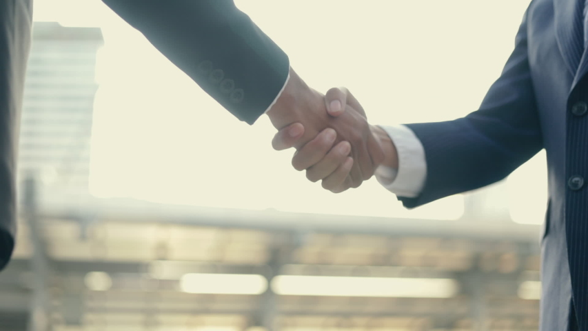 Asian businessman and businesswoman shaking hands partnership deal business while standing outside on the street near a big office building urban in the morning.