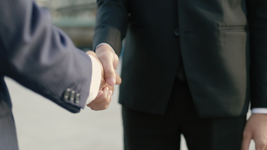 Close up hands asian business people in a black suit shaking hands partnership deal while standing outside on the street near a big office building urban.