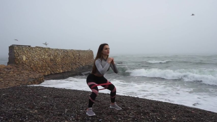 Girl performs physical exercises on the seashore.   Shutterstock HD Video #1043444230