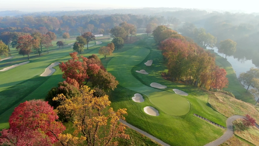 Slow tracking shot above golf course green, sand trap hazards, fall leaves and river