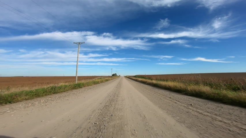 Point of view footage while driving down a gravel road in rural Iowa; visible are power lines, corn fields, barn, soybean fields and a wind turbines | Shutterstock HD Video #1043460244