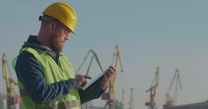 Port Worker With A Beard In A Yellow Helmet Stands With A Tablet PC In The Seaport  Against The Background Of Cranes. The Foreman Inspects The Industrial Harbor. Cinema 4K Video
