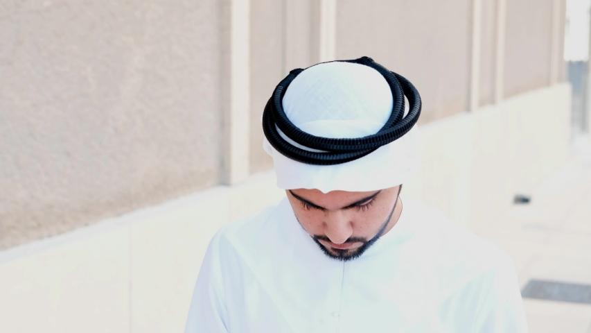 Arab man looks up to the camera smiling. Happy Arabic Emirati national smiles as he looks in front wearing Kandura. Middle Eastern guy on dish dasha UAE menswear