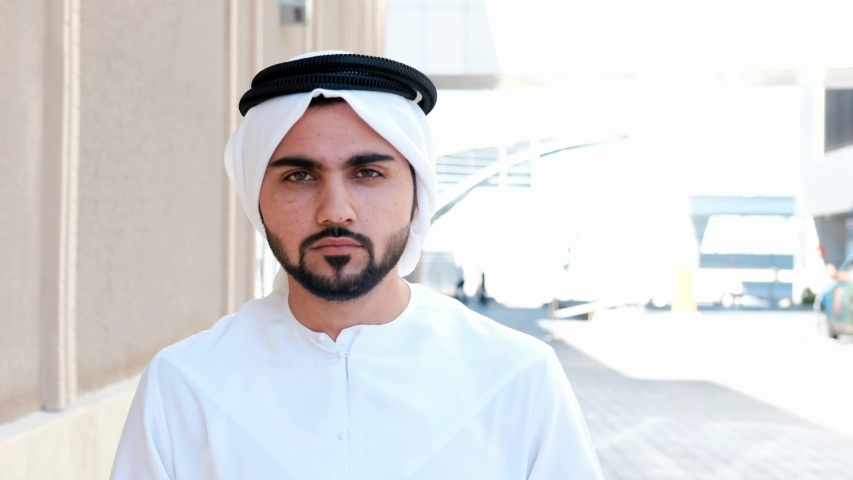 Walking Arab man wearing Kandura on business location. Arabic businessman walks on the city streets wearing dish dasha. Arabian Middle Eastern smiles while walking towards the front
