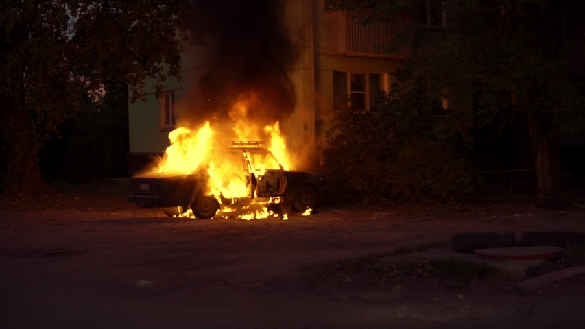 Burning car close to a house in a sleeping area of the city. Theme of riots criminal arson of a car near house. Automobile engulfed in flames of fire. Trees close to burning sedan.