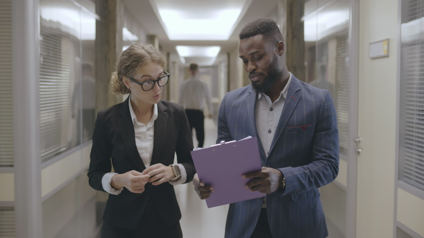 Multiracial young business people male and female discussing data from documents walking in office lobby before meeting. Royalty-Free Stock Footage #1043480839