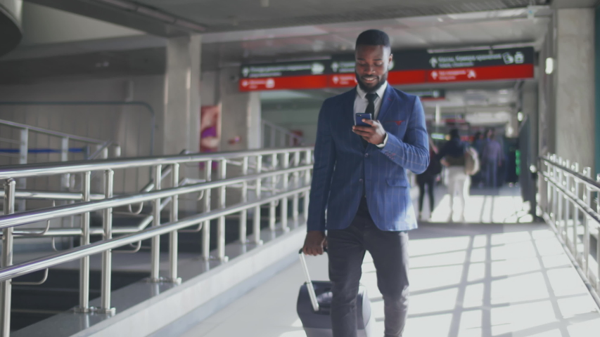 Elegant african businessman checking e-mail on mobile phone while walking with suitcase inside airport. Experienced male employer using cell phone while walking on train platform going for work travel Royalty-Free Stock Footage #1043480854