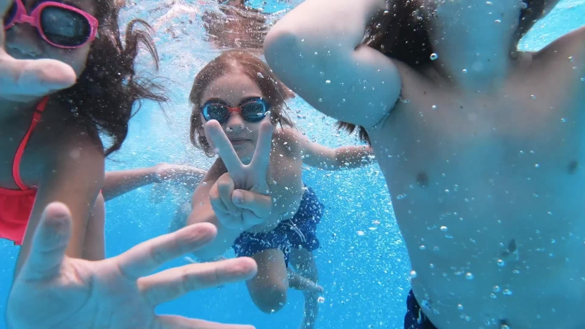 Children enjoying summer vacation. Happy fun loving group of friends jumping and diving into swimming pool at a pool party in summer sunny day. Slow motion. Underwater view Royalty-Free Stock Footage #1043487715