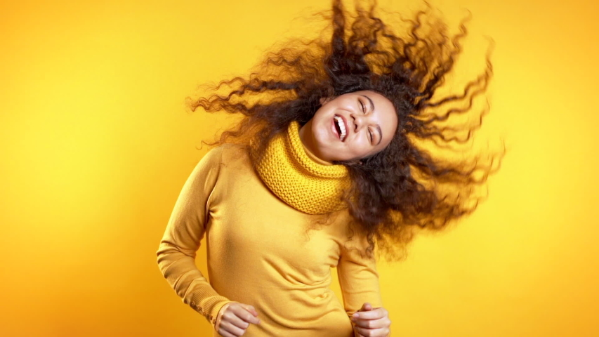 Young cute girl smiling and dancing on yellow studio background. Woman in colorful bright wear. Positive mood. Slow motion. | Shutterstock HD Video #1043524426