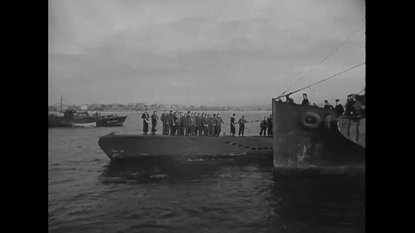CIRCA 1945 - German Naval POWs are transferred to a British submarine deck.