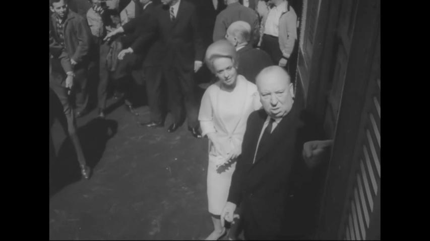 """CIRCA 1963 - Tippi Hedren and Alfred Hitchcock unleash a cage of pigeons at the New York City premiere of """"The Birds."""""""