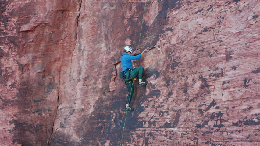 Female rock climber skillfully and technically moves up a steep sandstone wall | Shutterstock HD Video #1043547085
