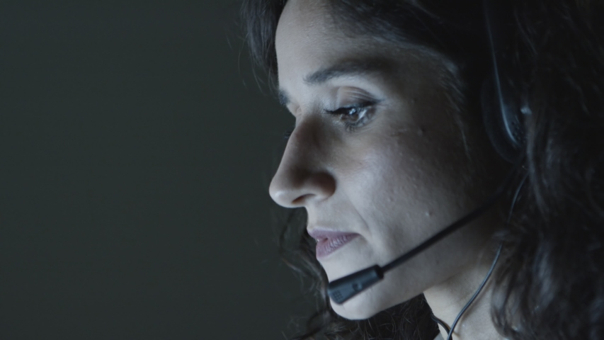 Female teleworker working at night. Close-up view of focused young female call center operator in headset talking and working in dark office. Client support concept   Shutterstock HD Video #1043551033
