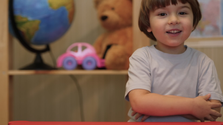 Kid Child Boy Making Online Video Call Recording Vlog Sitting by  Table , Portrait. Funny Boy Smiling Looking At Camera. Happy Cute Little Vlogger Saying Hello Hi Looking At Camera Talking To Webcam.