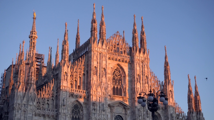 Cathedral of Milan or Duomo di Milano and street lamps in front of the gallery to Victor Emmanuel II in Piazza del Duomo. Balloons with helium. Evening sky over the gothic temple. Architetture | Shutterstock HD Video #1043600110