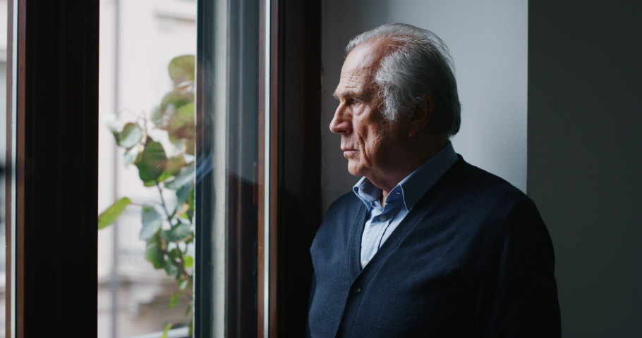An elderly thoughtful smiling man is looking out a window of his house in the morning.